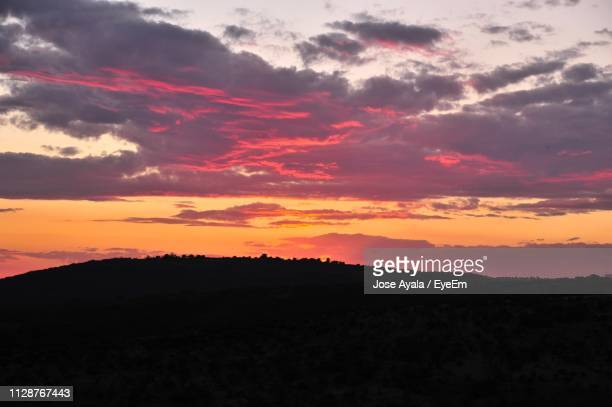 scenic view of dramatic sky over silhouette landscape - jose ayala stock pictures, royalty-free photos & images