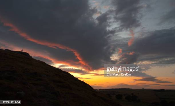 scenic view of dramatic sky over silhouette landscape - オトレイ ストックフォトと画像