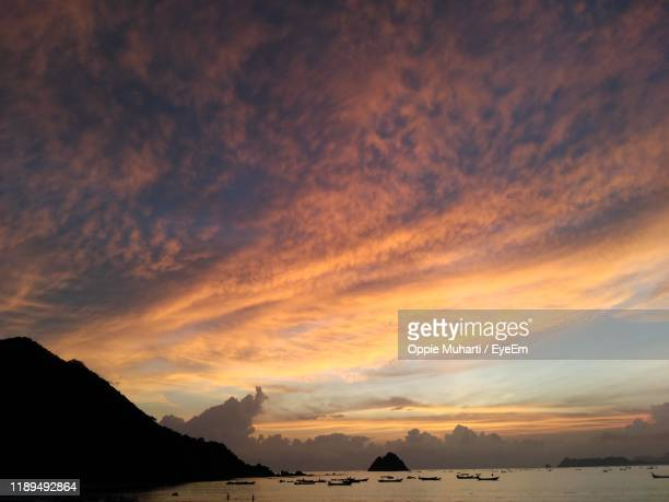 scenic view of dramatic sky over silhouette mountains during sunset - oppie muharti stock pictures, royalty-free photos & images