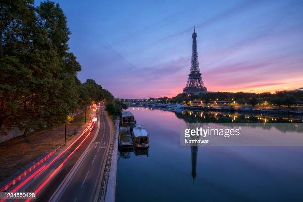 scenic view of eiffel tower over seine river during dramatic sunset, paris, france - uferviertel stock-fotos und bilder