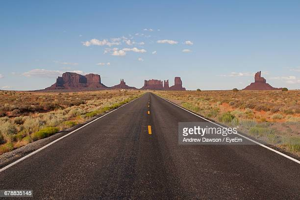 scenic view of empty road leading to rock formations - monument valley tribal park stock photos and pictures
