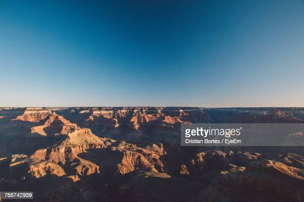 Scenic View Of Eroded Landscape Against Clear Blue Sky During Sunset