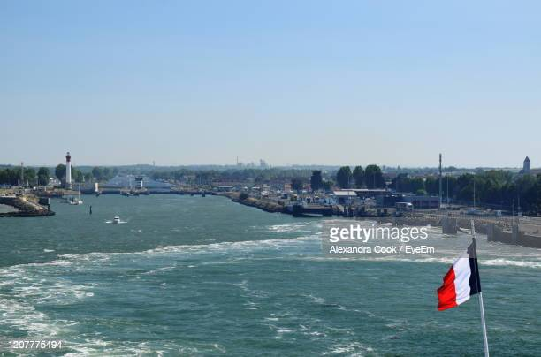 scenic view of estuary against clear sky with a flag - カルヴァドス県 ストックフォトと画像