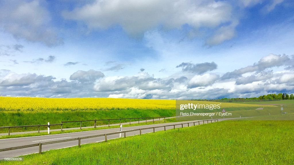Scenic View Of Farms Against Cloudy Sky : Stock Photo