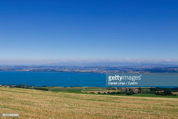 scenic view of field against clear blue sky - lausanne stock photos and pictures
