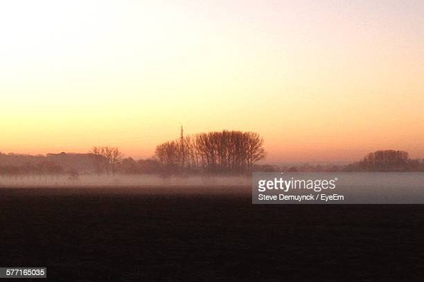 Scenic View Of Field Against Clear Sky At Sunrise