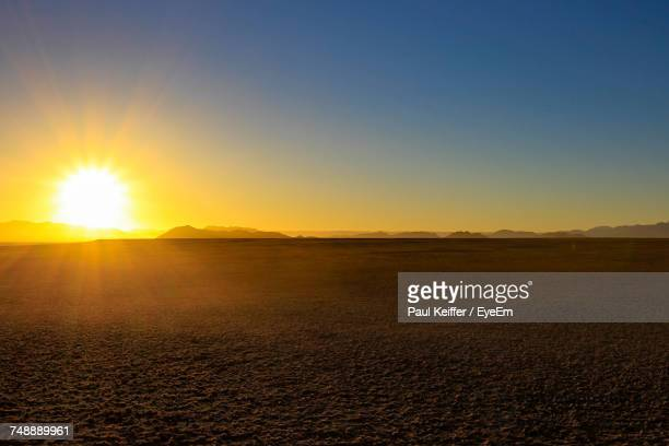 scenic view of field against clear sky during sunset - horizon over land stock photos and pictures