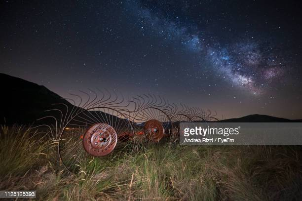 scenic view of field against sky at night - andrea rizzi stockfoto's en -beelden