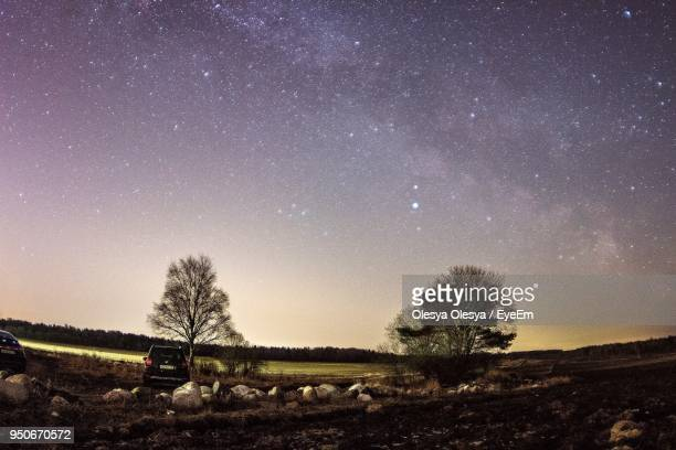 scenic view of field against sky at night - astronomy stock pictures, royalty-free photos & images