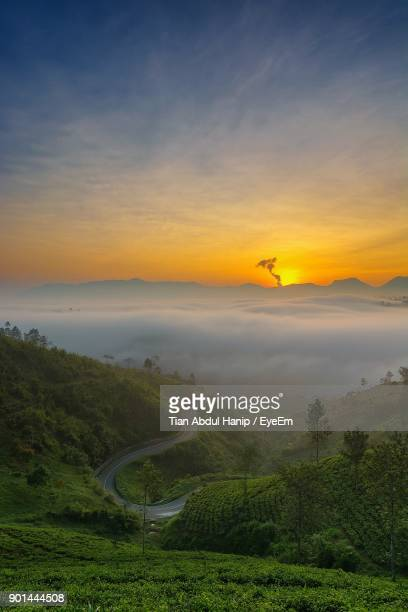 scenic view of field against sky at sunset - tian abdul hanip stock photos and pictures