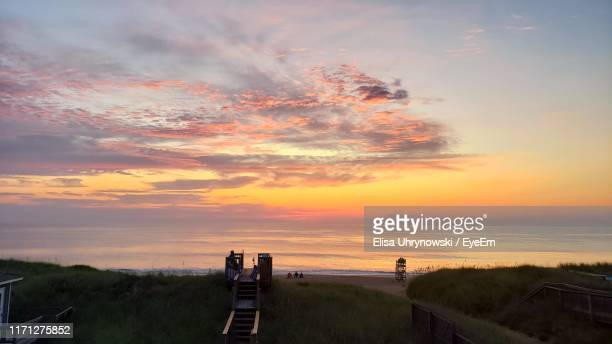 scenic view of field against sky during sunset - kitty hawk beach stock pictures, royalty-free photos & images