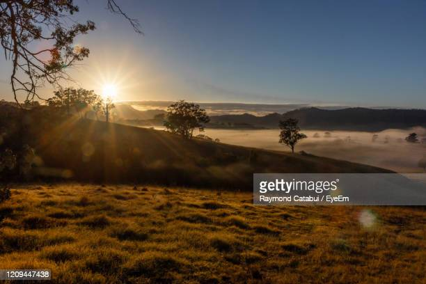 scenic view of field against sky during sunset - snowcapped mountain stock pictures, royalty-free photos & images