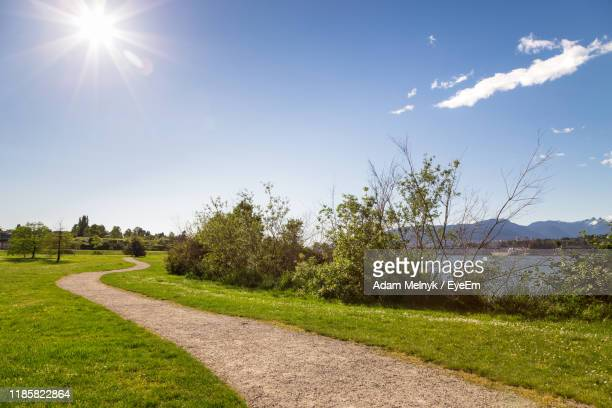 scenic view of field against sky on sunny day - natural parkland stock pictures, royalty-free photos & images