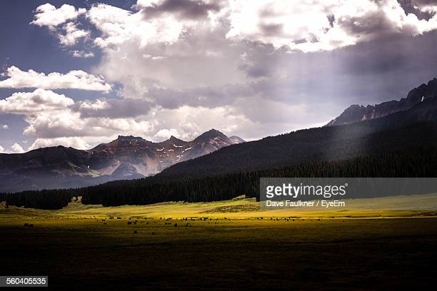 Scenic View Of Field And Mountains Against Cloudy Sky