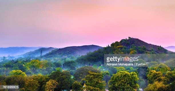 Scenic View Of Field And Mountains Against Sky During Sunset