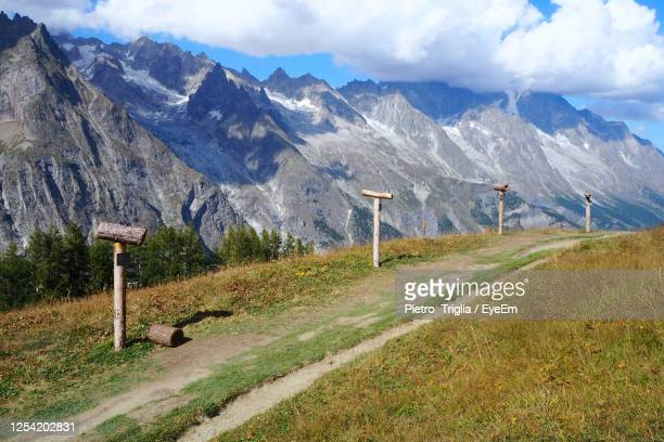 scenic view of field and mountains against sky - valle d'aosta foto e immagini stock