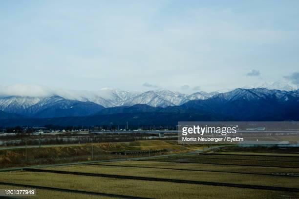 scenic view of field and snowcapped mountains against sky - 富山県 ストックフォトと画像