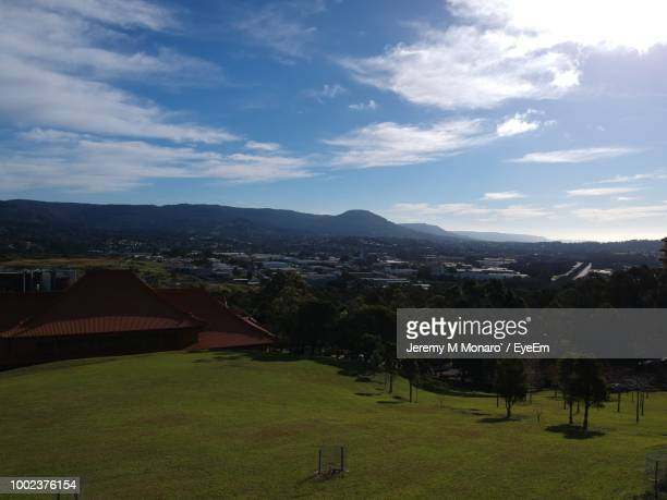 scenic view of field by houses against sky - jeremy monaro stock pictures, royalty-free photos & images