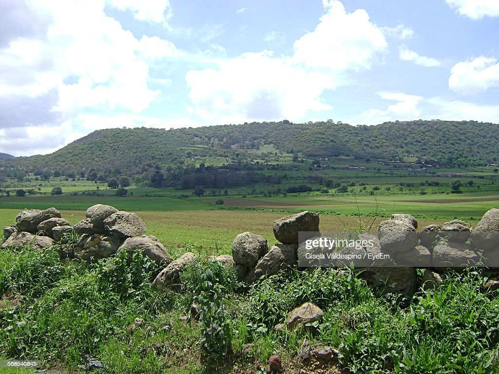 Scenic View Of Field By Mountain Against Cloudy Sky : Stock Photo