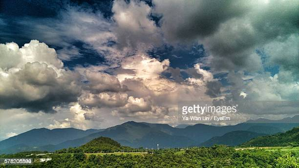 Scenic View Of Field By Mountains Against Cloudy Sky