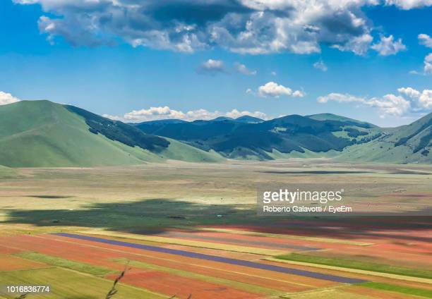 scenic view of field by mountains against sky - castelluccio stock photos and pictures