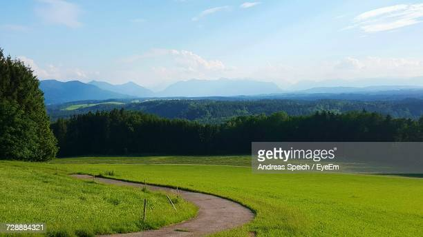 Scenic View Of Field By Mountains Against Sky