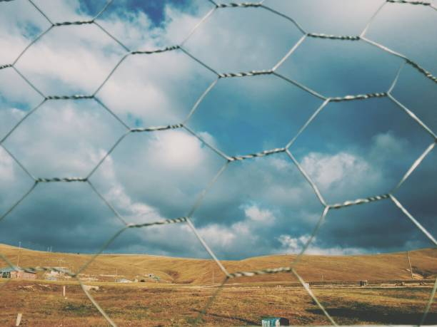 Scenic View Of Field Seen Through Chainlink Fence