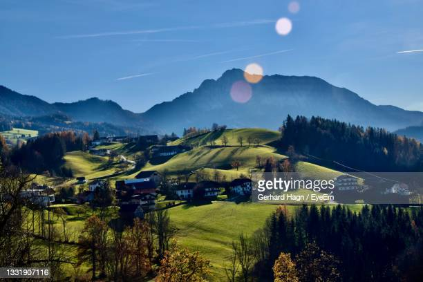 scenic view of fields with farm houses and trees against mountains and sky - gerhard hagn stock-fotos und bilder