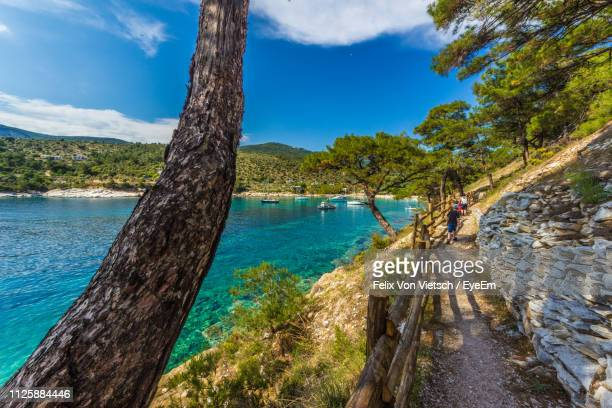 scenic view of footpath by lake against sky - thasos stock photos and pictures