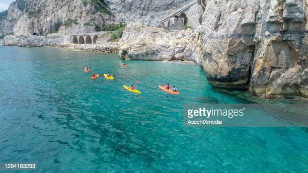 scenic view of friends sea kayaking in the morning - sea kayaking stock pictures, royalty-free photos & images