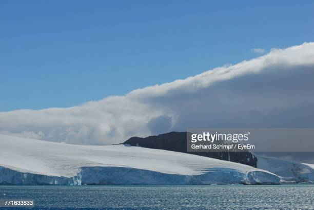 scenic view of frozen lake against blue sky - gerhard schimpf stock pictures, royalty-free photos & images