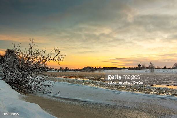 scenic view of frozen lake against sky during sunset - heinovirta stock pictures, royalty-free photos & images