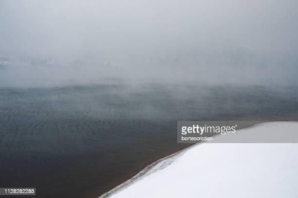 scenic view of frozen lake against sky during winter - bortes foto e immagini stock