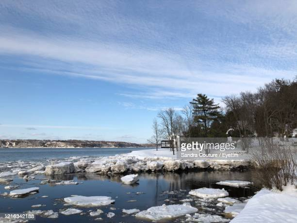 scenic view of frozen lake against sky - lévis quebec stock pictures, royalty-free photos & images