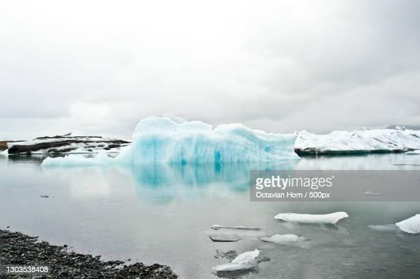 scenic view of frozen lake against sky - 氷河湖 ストックフォトと画像