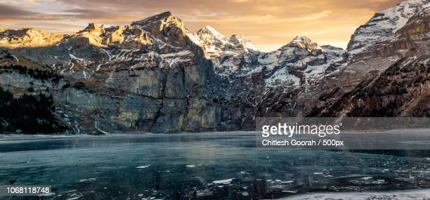 scenic view of frozen lake and mountains of bernese alps in winter at sunset - ヌーシャテル ストックフォトと画像