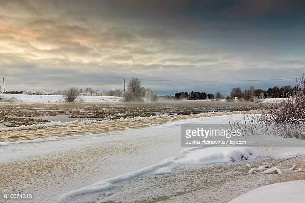 scenic view of frozen river against cloudy sky - heinovirta stock pictures, royalty-free photos & images