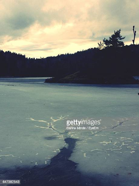 Scenic View Of Frozen River Against Cloudy Sky