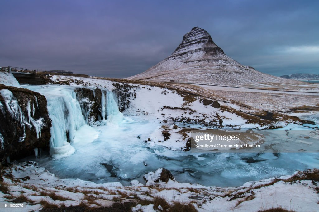Scenic View Of Frozen Waterfall And Mountain Against Sky : Stock Photo