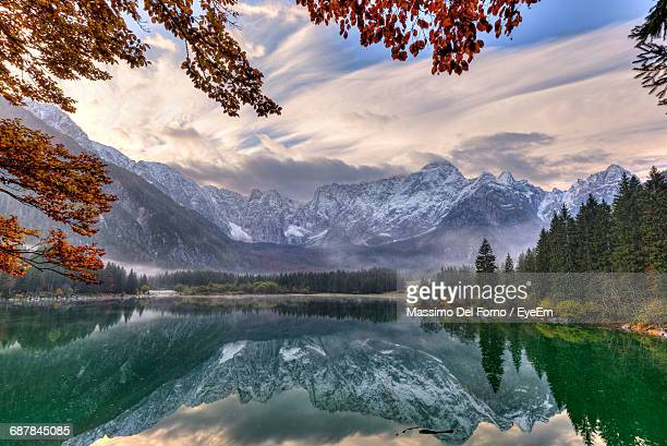 Scenic View Of Fusine Lake Against Cloudy Sky Reflected In Water