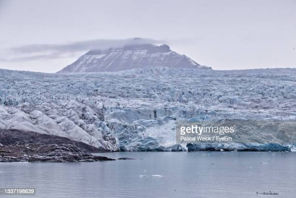 scenic view of glacier and snow capped mountains in the arctic against sky - svalbard and jan mayen stock pictures, royalty-free photos & images