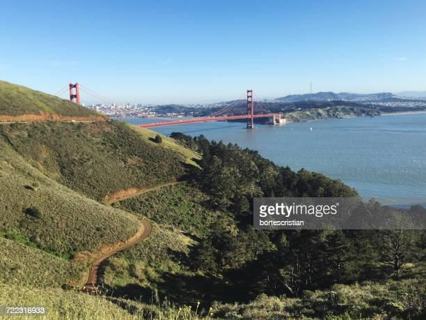 scenic view of golden gate bridge over san francisco bay against blue sky - bortes bildbanksfoton och bilder