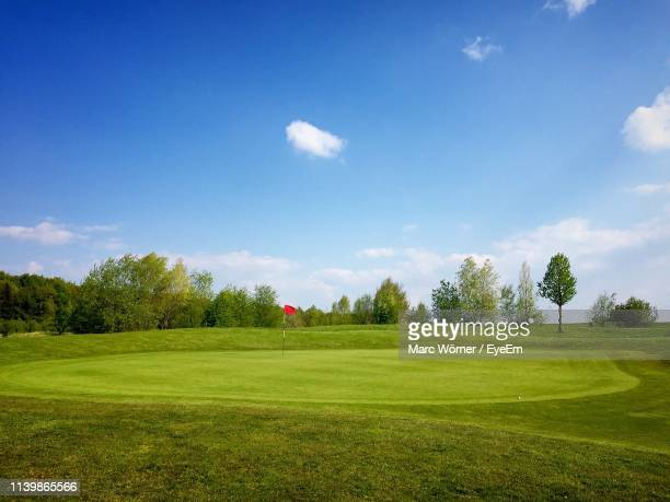 scenic view of golf course against blue sky - golf flag stock pictures, royalty-free photos & images