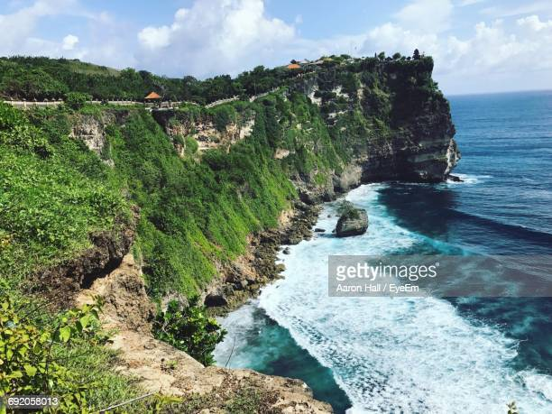 Scenic View Of Grassy Cliff By Sea
