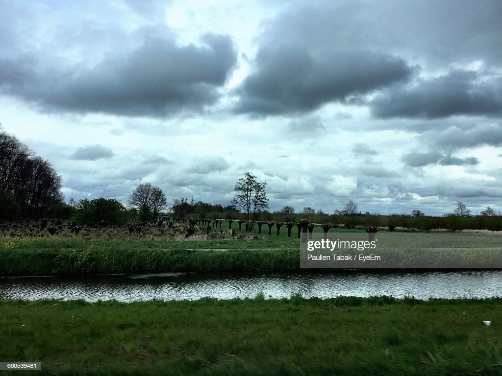 Scenic View Of Grassy Field Against Cloudy Sky : Stockfoto