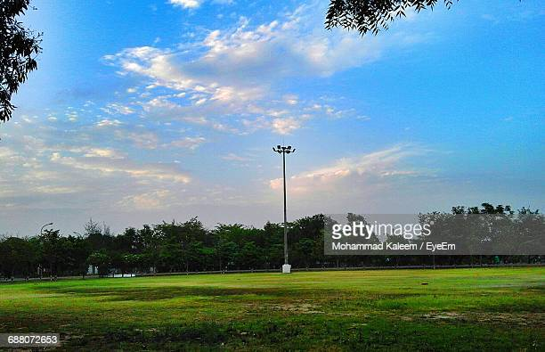 scenic view of grassy field against cloudy sky - cricket pitch stock pictures, royalty-free photos & images