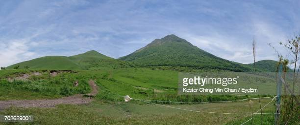 scenic view of grassy field against cloudy sky - 別府市 ストックフォトと画像