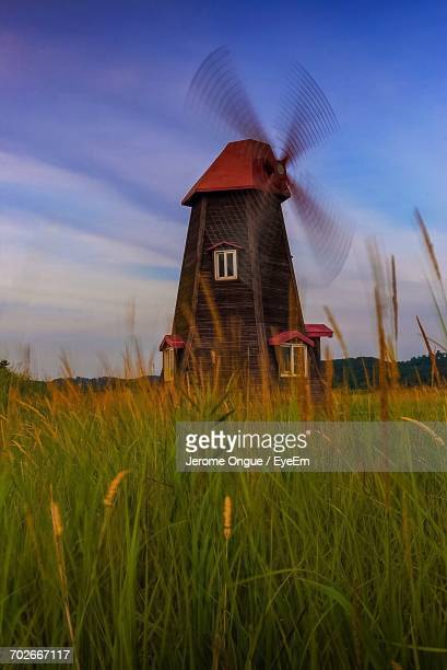 scenic view of grassy field against cloudy sky - traditional windmill stock photos and pictures
