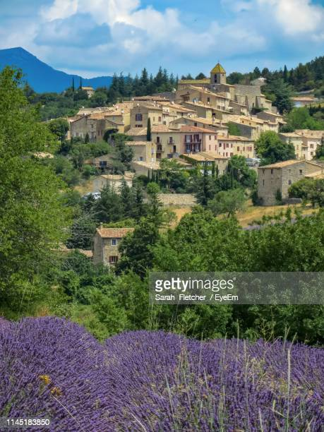 scenic view of grassy field by buildings against cloudy sky - aix en provence stock pictures, royalty-free photos & images