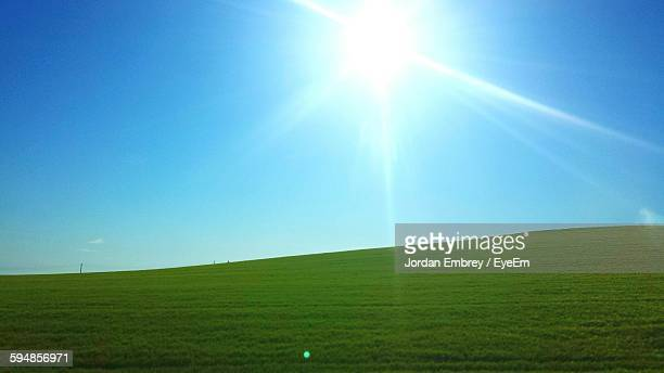 Scenic View Of Grassy Landscape Against Bright Sky